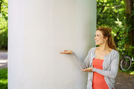 Smiling woman holding out her empty hands to the side standing in front of a white outdoor pillar looking to empty copy space