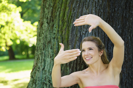 Pretty woman making a frame gesture with her hands as she tries to visualise something with standing under a tree in a leafy green park Stock Photo