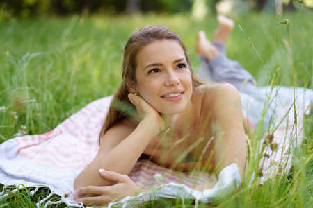 Young woman lying daydreaming in the grass lying on a rug looking up into the air with a dreamy expression