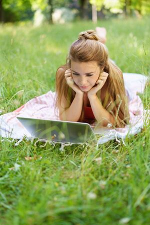 Young long-haired woman lying on blanket in park using laptop