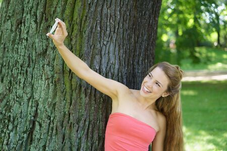 Young cheerful woman standing by tree in park taking selfie