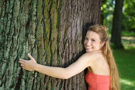 Portrait of young smiling woman embracing large tree in park