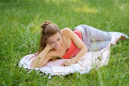 Pretty young woman lying reading a book outdoors on a rug in long green grass smiling with pleasure Stock Photo
