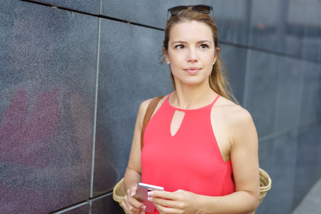 Thoughtful attractive woman walking in town alongside a grey wall of a commercial building looking pensively to the side