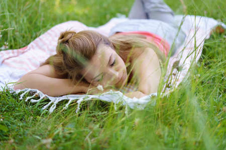 Young woman spending a relaxing day outdoors lying sleeping on a rug in long green grass in a low angle view Stock Photo