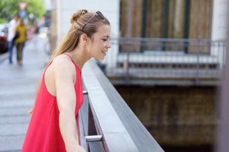 Young woman looking over an urban bridge into the canal below with an interested expression as she watches something Stock Photo