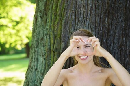 Young woman with bare shoulders making a heart gesture with her fingers as she stands in the shade of a tree in a green park