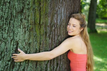 Young smiling woman taking natural energy from tree in park Stock Photo