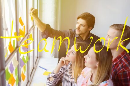 Office colleagues brainstorming ideas using sticky notes in a teamwork themed concept with yellow writing over the top. Stock Photo