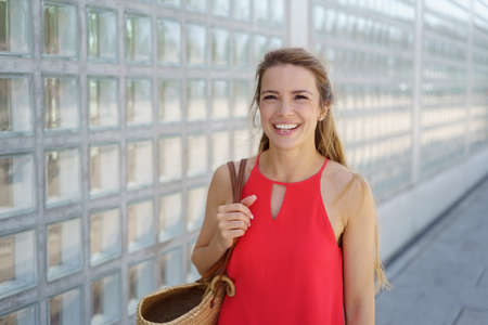 Happy young woman in red walking through town alongside a feature wall with a friendly smile and copy space Stock Photo