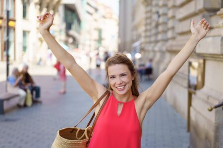 Happy young woman rejoicing with outstretched arms and a happy smile as she walks down an urban street Stock Photo