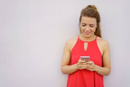 Portrait of young smiling woman wearing red dress using mobile phone against white wall with copy space Stock Photo