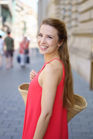 Outdoor portrait of young cheerful woman wearing red dress with bag Stock Photo