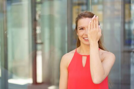 Young woman covering one eye with her hand with a smile as she stands in front of glass windows of a commercial building