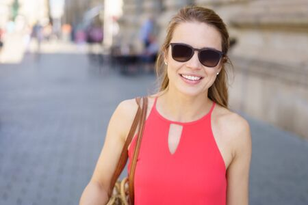 Outdoors portrait of young smiling woman wearing red dress with sunglasses Stock Photo