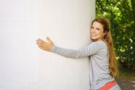 Cheerful young woman hugging a white pillar with copy space in a leafy green garden Stock Photo