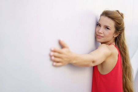 Attractive quiet calm young woman stretching out her arms on a wall looking at the camera with a thoughtful expression Stock Photo