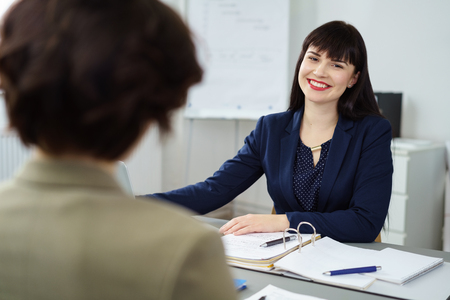 Happy young businesswoman smiling at a colleague as they sit having a discussion at a table in the office in an over the shoulder view