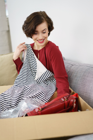 Cute young woman unpacking new clothing form a cardboard box that have been sent as a gift or order as she sits on a sofa Stock Photo