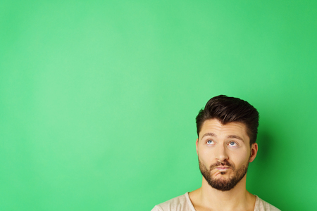 Headshot of young pensive bearded man looking up against green background with copy space