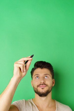 Thinking concept of young man drawing in air using pencil with copy space against green background