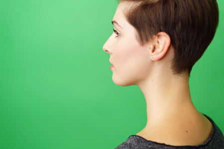 Profile portrait of young short-haired serious woman against green background