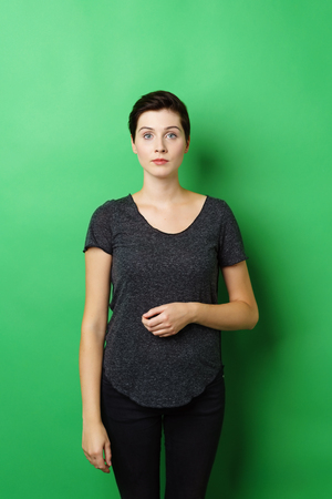 Young serious woman standing upright against green background with bent arm