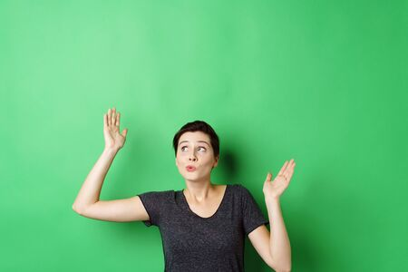 Young short-haired woman standing with hands up against chroma key green screen with copy space, looking up with whistling surprise grimace, as if she looking at invisible objects