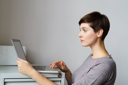 Profile portrait of young woman standing by file cabinet with laptop at office Stock Photo