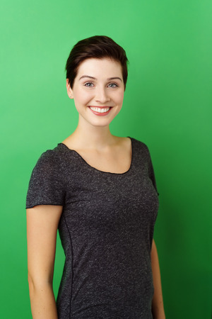 Young smiling dark-haired woman standing against green background Banque d'images