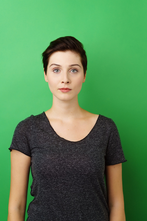 Young serious dark-haired woman standing against green background Stock Photo