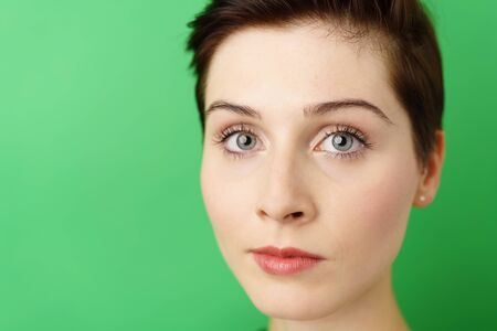 Headshot of young dark-haired woman looking at camera against green background Stock Photo