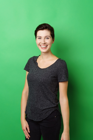 Three quarter length portrait of young cheerful woman standing upright against green background Stock Photo