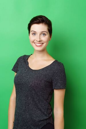 Waist up portrait of young smiling woman standing against green background