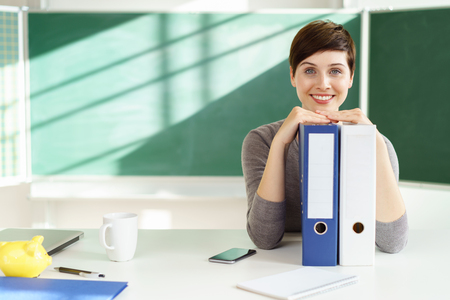 Young smiling female teacher sitting with binders against blackboard in classroom Stock Photo