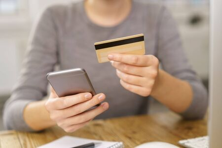 technology transaction: Woman making an online purchase on her mobile phone entering the details of her bank card in a close up view of her hands Stock Photo