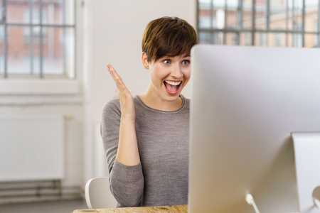 Young surprised enthusiastic woman sitting in front of computer