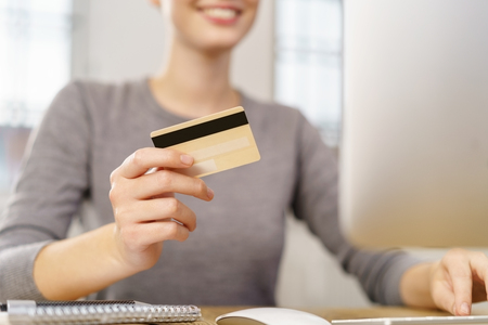 Smiling woman sitting at desk in front of computer with credit card
