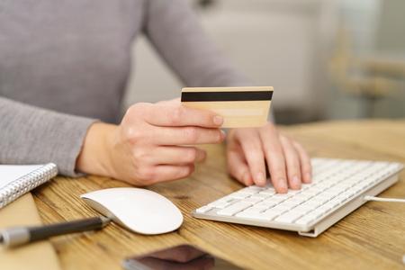 Frau, die online Käufe eingibt, die ihre Bankkartendetails eingeben, während sie ihr Einkaufen abschließt Standard-Bild - 89273563