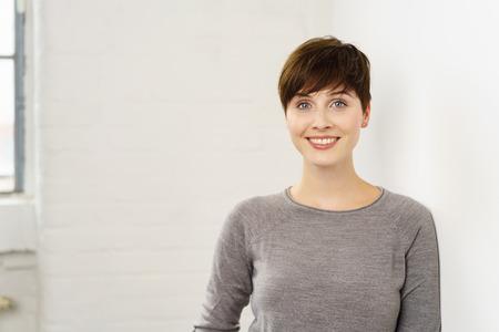 Glimlachende pert aantrekkelijke jonge vrouw die de camera met een richtende glimlach in een hoofd en schoudersportret bekijkt tegen een witte muur