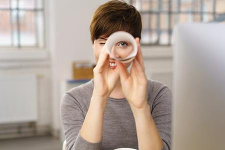 Grimaçant jeune femme d'affaires d'espionnage sur la caméra en regardant à travers une feuille roulée de papier blanc comme elle s'assied à son bureau