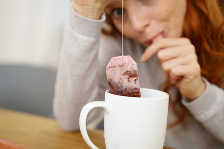 Woman brewing a fresh mug of tea leaning down to watch the teabag with anticipation with focus to the beverage Stock Photo