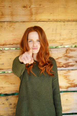 Young woman pointing at the camera with a serious face in accusation or identifying someone or something over a rustic wood background with copy space