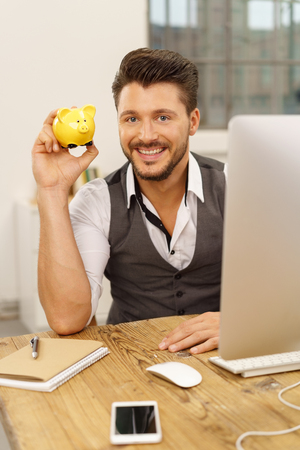 Happy successful businessman holding up a piggy bank as he sits at his desk at the office conceptual of profits, savings and achievement