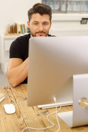 Portrait of a creative young man working with concentration on a desktop computer while sitting at a wooden desk in a modern office Stock Photo