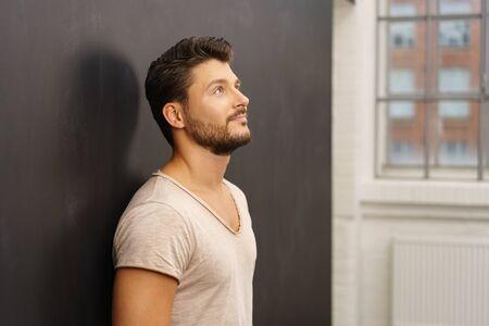瞑想的な表情で見上げる暗い灰色の壁に思慮深い男立っているもたれ 写真素材