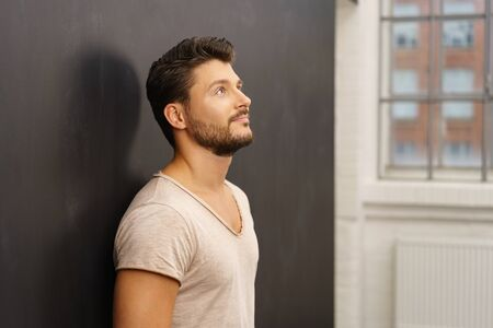Thoughtful man standing leaning against a dark grey wall looking up with a contemplative expression