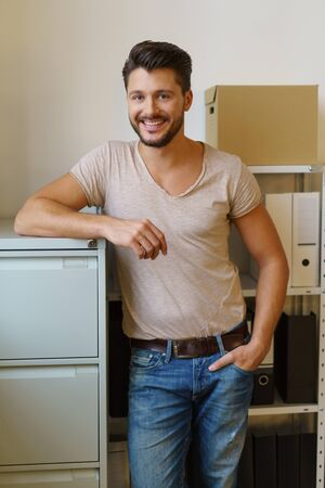 Portrait of young smiling bearded man leaning against filing cabinet in office