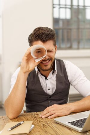 Businessman having fun playing I Spy looking at the camera through a rolled sheet of paper with a happy smile Stok Fotoğraf
