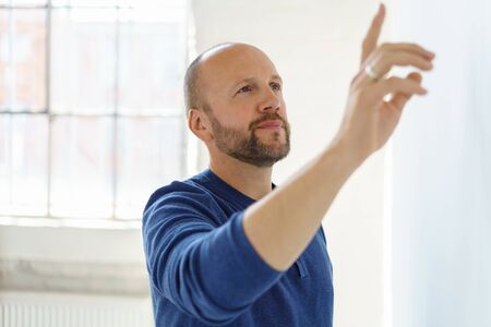 Thoughtful man pointing at something above him as he stands facing a white interior wall in a close up view